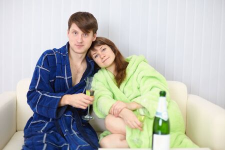 dressing gowns: Young couple in dressing gowns sitting on the couch with fizz Stock Photo