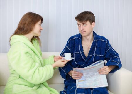 dressing gowns: Young couple in dressing gowns sitting on the couch Stock Photo