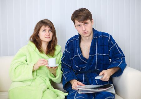 dressing gowns: Young couple in dressing gowns sitting on the couch and watching TV in disgust Stock Photo