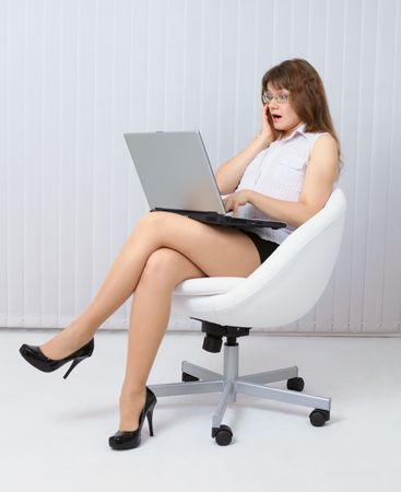 Woman in horror sits in a white chair with laptop photo