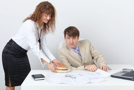 Young people are having dinner at the workplace in a light office photo