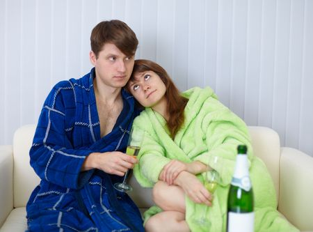 dressing gowns: Young people sit at home on the couch in dressing gowns with fizz