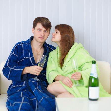 dressing gowns: Young people sit at home on the sofa in dressing gowns with fizz