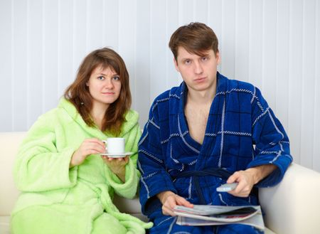 dressing gowns: Couple sit on the sofa in dressing gowns and watching TV in disgust Stock Photo