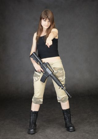 A young woman armed with a rifle standing on a black background photo