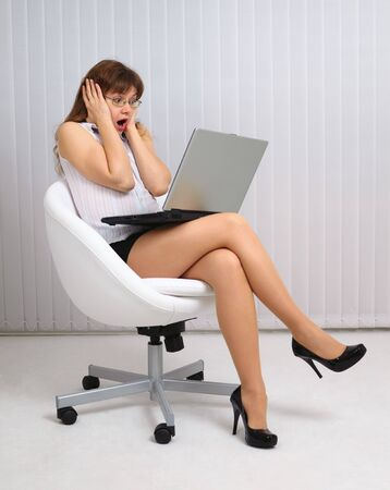 Woman in horror looking at the laptop screen photo