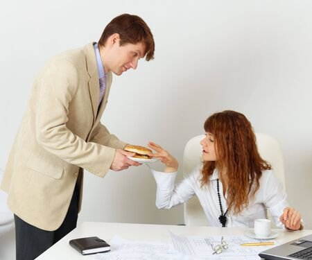 A man treats a woman colleague hamburger photo