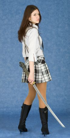 Female teenager armed with katana on a blue background photo