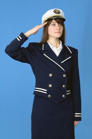 salutes: The girl in a sea uniform salutes on blue background Stock Photo