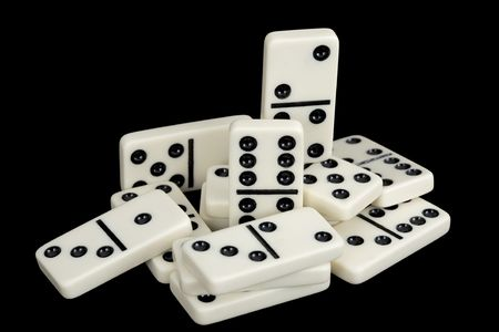 precarious: A bunch of dominoes isolated on a black background Stock Photo