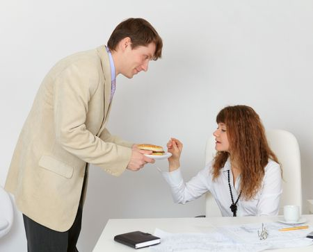 Man feeding woman a sandwich in the office photo