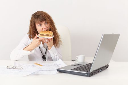 eagerly: Young woman eagerly have a sandwich in the workplace Stock Photo
