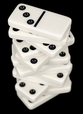 precarious: A stack of dominoes isolated on a black background Stock Photo