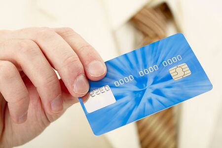Businessman shows a blue plastic credit card Stock Photo - 6436267