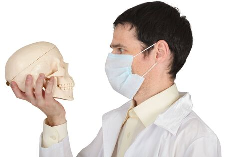 medical school: Student medical school in the mask looks at human skull