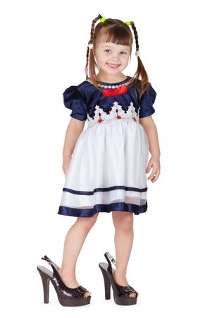 Funny little girl in her mother's big shoes isolated on white background Stock Photo - 6470911