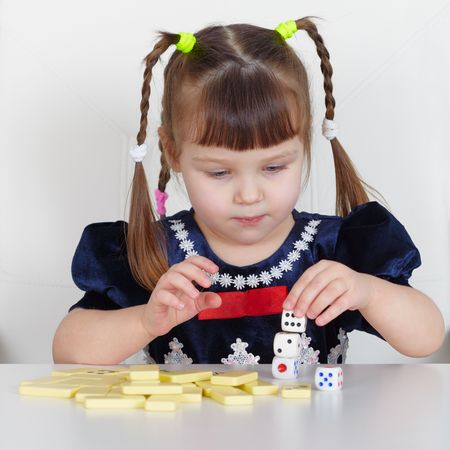 A child playing with small toys, sitting at the table Stock Photo - 6470904