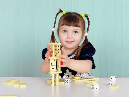 A child playing with small toys, sitting at the table photo
