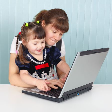 Mom teaches daughter to use a laptop Stock Photo - 6470952