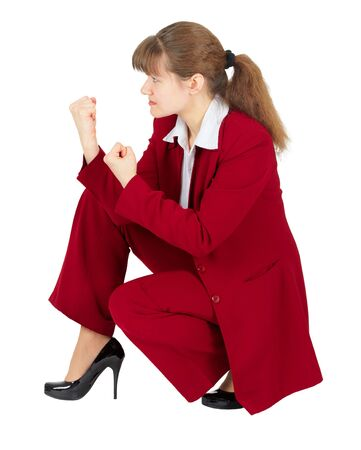 A woman in a red business suit sitting in a combat stance photo