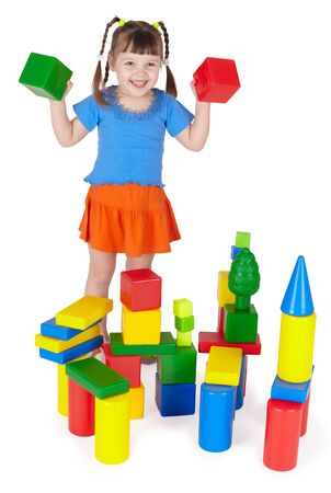 Cheerful girl playing with colored blocks on white photo
