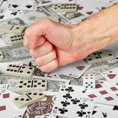 The hand clenched in a fist against the background of cards and money. photo