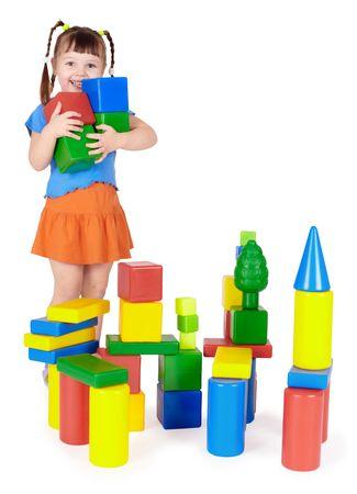 Happy child builds a castle out of color blocks photo