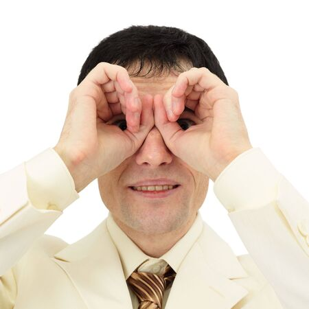 Businessman looking through his fingers like a pair of binoculars photo