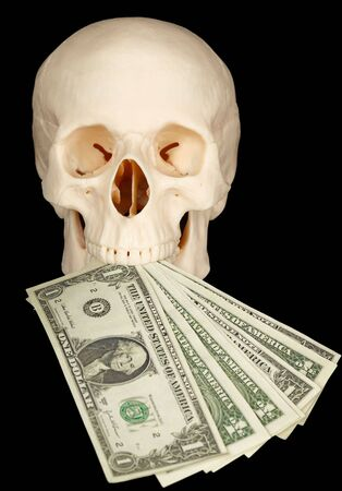 bared teeth: Horrible skull with a bundle of money in his mouth on a black background