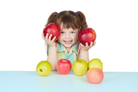 Funny child playing with two red apples on blue table photo