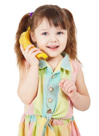 Child uses a banana as a mobile phone isolated on white photo