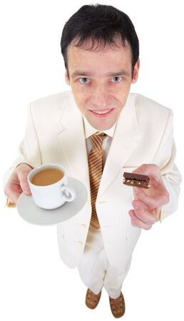 Funny young man is drinking coffee with sweets on white photo