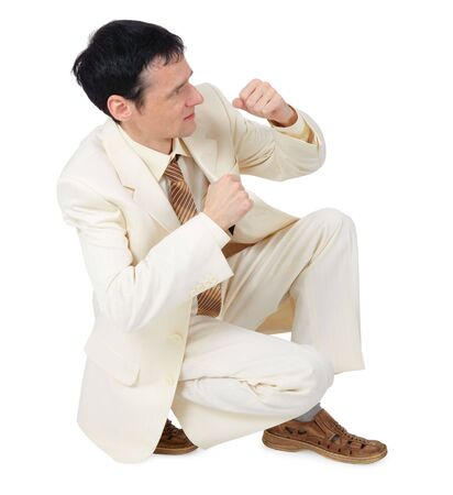 defensive posture: Businessman sitting in a defensive posture on a white background