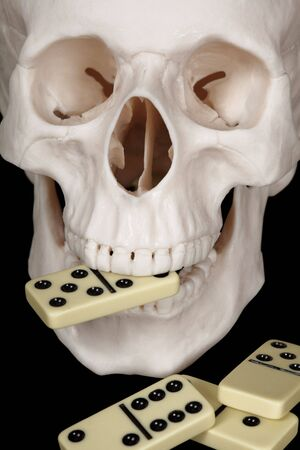 The skull clutched in his teeth dominoes isolated on a black background Stock Photo - 6709454