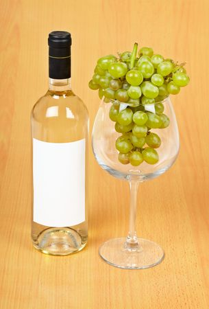 spirituous beverages: A bottle of wine, a large glass and grapes on wooden background