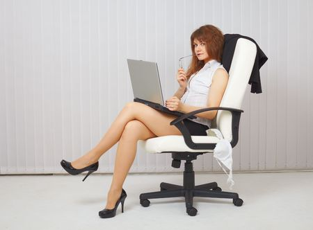 Sexy young woman with a computer in an office chair photo