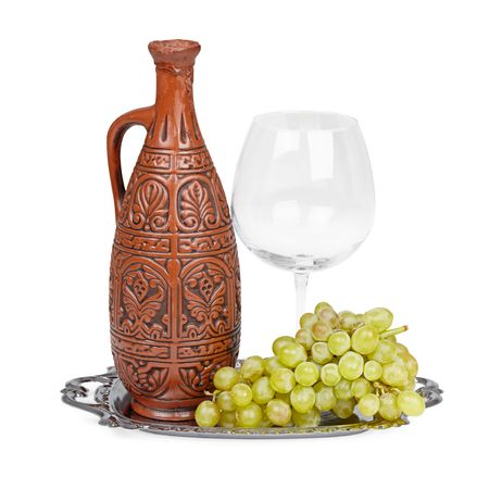 spirituous beverages: Still life of ceramic bottle, grapes and a glass on tray