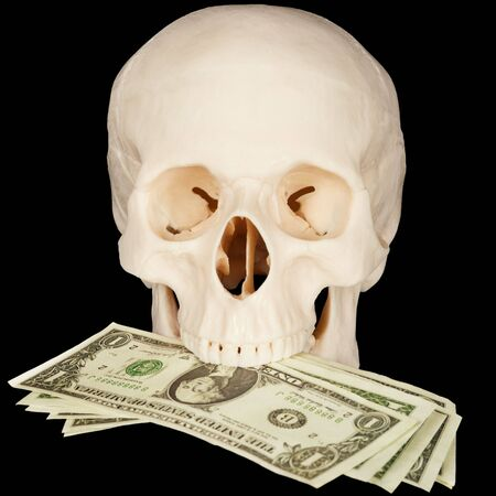 bared teeth: The skull clutched in teeth a bunch of money on a black background