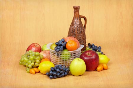 spirituous beverages: Still life of fruit and ceramic bottle of wine