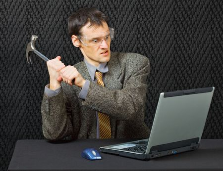 Comical person intends to break the computer with a hammer Stock Photo - 6828482