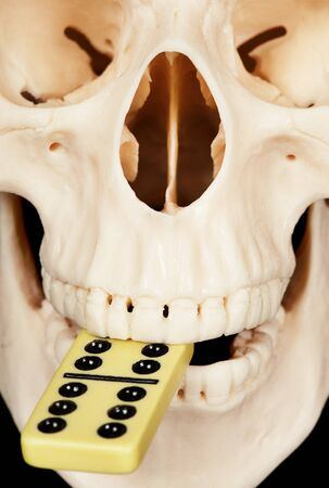 bared teeth: The human skull with dominoes in mouth