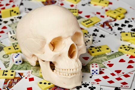 bared teeth: The skull on a background of playing cards, dominoes and money