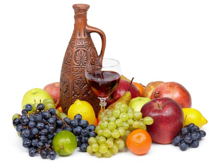 citrous: Artistic composition of fruit and jug of wine on white