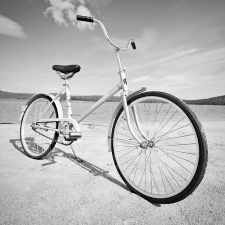 water wheel: Old old-fashioned bicycle on the beach - a monochrome picture Stock Photo