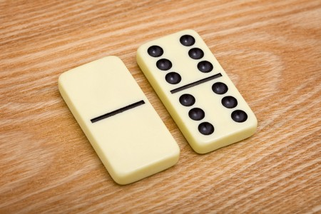 Two different dominoes on a wooden background photo