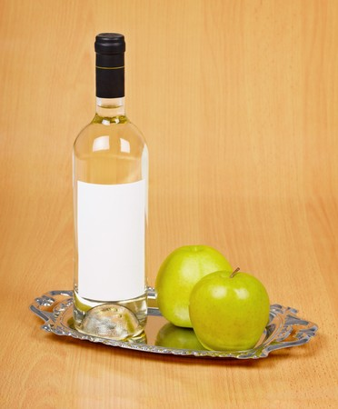 spirituous beverages: Apple wine in the closed bottle on a metal tray