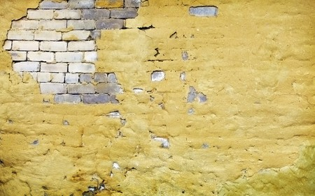 The brick yellow wall with broken plaster photo