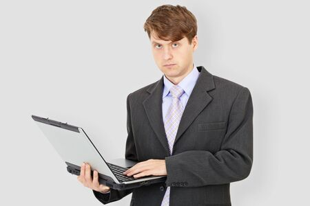 The business man with the laptop on a grey background photo