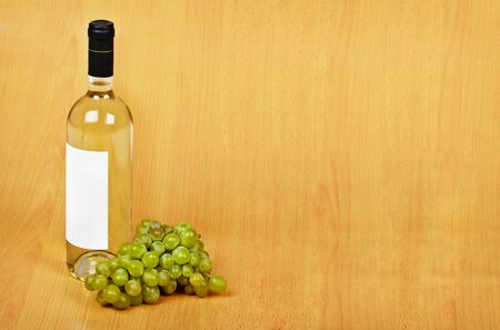 spirituous beverages: The open arrangement of bottle of white wine on a wooden background