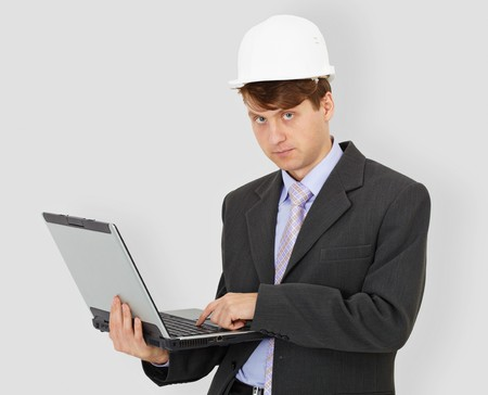 superintendent: The construction superintendent with the computer in hands in a helmet on a grey background